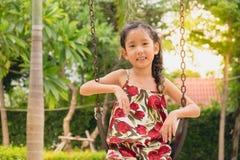 Bambina felice su oscillazione, fronte sorridente immagine stock