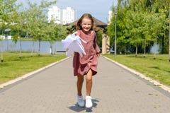 Bambina felice sveglia in vestito da Borgogna che corre con l'ombrello bianco fotografia stock