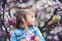 Bambina in giardino sbocciante il giorno di molla fotografie stock