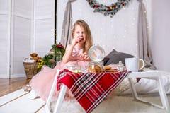 Bambina graziosa 4 anni in un vestito rosa Bambino nella stanza di Natale con un letto, mangiante caramella, cioccolato, i biscot fotografie stock