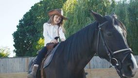 Bambina graziosa in cappello che guida una giumenta nera sull'arena 4K archivi video