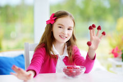Bambina graziosa che mangia i lamponi a casa Bambino sveglio che gode della sue frutta fresca e bacche sane Fotografia Stock Libera da Diritti