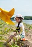 Bambina graziosa che posa con il mulino a vento in parco Immagini Stock Libere da Diritti