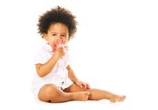 Bambina graziosa che sente l'odore di un fiore Fotografia Stock Libera da Diritti