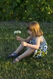 Bambina graziosa che si siede nel prato inglese che tiene un piccolo mazzo dei wildflowers immagini stock