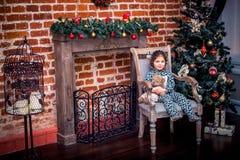 Bambina graziosa che sorride con l'orsacchiotto vicino all'albero di Natale che si siede nella sedia d'annata Nuovo anno felice Fotografie Stock Libere da Diritti