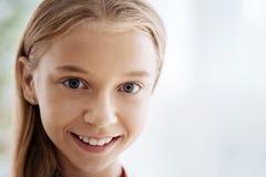 Bambina graziosa che sorride e che sembra felice fotografia stock