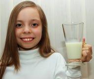 Bambina graziosa con il sorriso bianco come la neve e una tazza di latte in sua mano Fotografia Stock