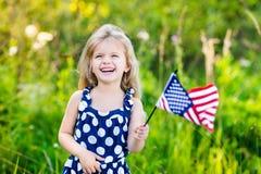 Bambina graziosa con la bandiera americana riccia della tenuta dei capelli biondi Fotografie Stock Libere da Diritti