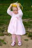 Bambina graziosa con la ghirlanda del fiore del dente di leone. Fotografie Stock