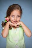 Bambina graziosa contro il blu Fotografia Stock