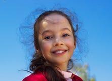 Bambina graziosa contro il fondo blu del cielo di estate Immagine Stock