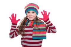 Bambina graziosa sorridente che indossa sciarpa tricottata variopinta, cappello ed i guanti isolati su fondo bianco Vestiti di in Fotografia Stock