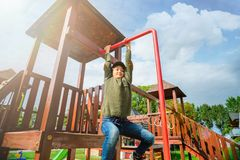 Bambina impavida curiosa che scala sul campo da giuoco da solo in tempo soleggiato Immagini Stock