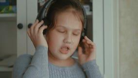 Bambina impressionabile La bambina con il dancing lungo dei capelli con le cuffie su una casa stock footage