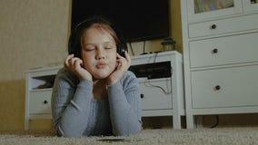 Bambina impressionabile La bambina con il dancing lungo dei capelli con le cuffie su una casa archivi video