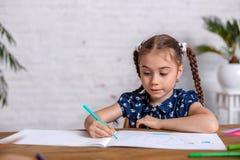 Bambina ispirata al tiraggio della tavola con i pastelli o fare lavoro domestico immagine stock libera da diritti