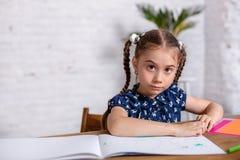 Bambina ispirata al tiraggio della tavola con i pastelli o fare lavoro domestico fotografia stock
