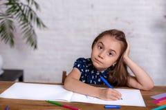 Bambina ispirata al tiraggio della tavola con i pastelli o fare lavoro domestico fotografia stock libera da diritti