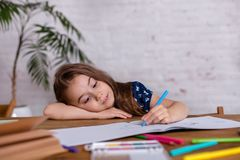 Bambina ispirata al tiraggio della tavola con i pastelli o fare lavoro domestico immagini stock libere da diritti