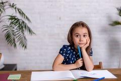 Bambina ispirata al tiraggio della tavola con i pastelli o fare lavoro domestico immagine stock