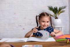 Bambina ispirata al tiraggio della tavola con i pastelli o fare lavoro domestico fotografie stock libere da diritti