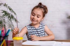 Bambina ispirata al tiraggio della tavola con le pitture fotografia stock libera da diritti