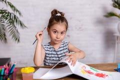 Bambina ispirata al tiraggio della tavola con le pitture fotografie stock libere da diritti