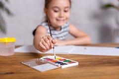 Bambina ispirata al tiraggio della tavola con le pitture fotografia stock