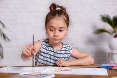 Bambina ispirata al tiraggio della tavola con le pitture immagini stock