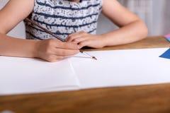 Bambina ispirata al tiraggio della tavola con le pitture Primo piano immagine stock