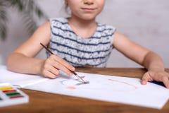 Bambina ispirata al tiraggio della tavola con le pitture Primo piano fotografia stock