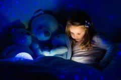 Bambina a letto con la lampada di notte Fotografia Stock Libera da Diritti