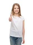Bambina in maglietta bianca in bianco che mostra thumbsup Immagine Stock