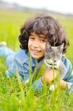Bambina molto sveglia con il gatto sul prato Fotografia Stock