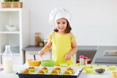 Bambina in muffin di cottura del toque dei cuochi unici a casa fotografia stock