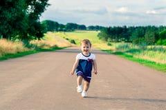 Bambina nei ress che corre verso la strada e le risate Fotografie Stock Libere da Diritti