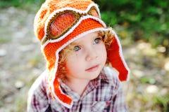 Bambina nel cappuccio arancio del pilota e degli occhiali di protezione di volo Fotografia Stock Libera da Diritti