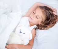 Bambina nel letto con l'orsacchiotto Fotografia Stock Libera da Diritti