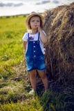 Bambina nel mucchio di fieno in un cappello fotografia stock