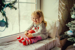 Bambina nel Natale con la palla rossa delle decorazioni di Natale che si siede su una finestra Fotografie Stock