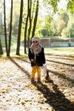 Bambina nel parco con la valigia Immagine Stock