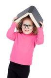 Bambina nel rosa con i vetri e un libro sulla sua testa Fotografie Stock