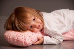 Bambina nel vestito di sonno che si trova su un cuscino Fotografia Stock