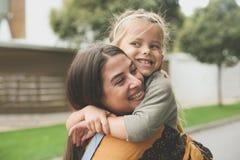 Bambina nell'abbraccio delle mamme fotografia stock