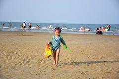 Bambina nella passeggiata del vestito di nuoto sulla sabbia con i giocattoli Fotografia Stock Libera da Diritti