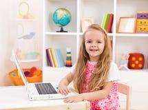 Bambina nella sua stanza che lavora al computer portatile Fotografia Stock Libera da Diritti