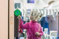 Bambina nella traccia moderna del passeggero Scherzi la condizione alla via di accesso principale ed al bottone commovente per ap fotografia stock