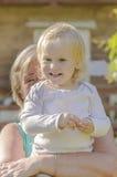 Bambina nelle armi di una donna Fotografia Stock