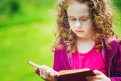 Bambina in occhiali che legge il libro nel parco di autunno Educa Immagini Stock Libere da Diritti